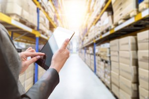 Horizontal color image of female hands holding a digital tablet in a corridor of futuristic distribution warehouse. Ordering online from a modern warehouse on a touchscreen tablet computer. Large distribution storage in background with racks full of packages, boxes, pallets, crates ready to be delivered. Logistics, freight, shipping, receiving.