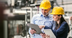 A portrait of an industrial man and woman engineers with tablet in a factory checking documents.